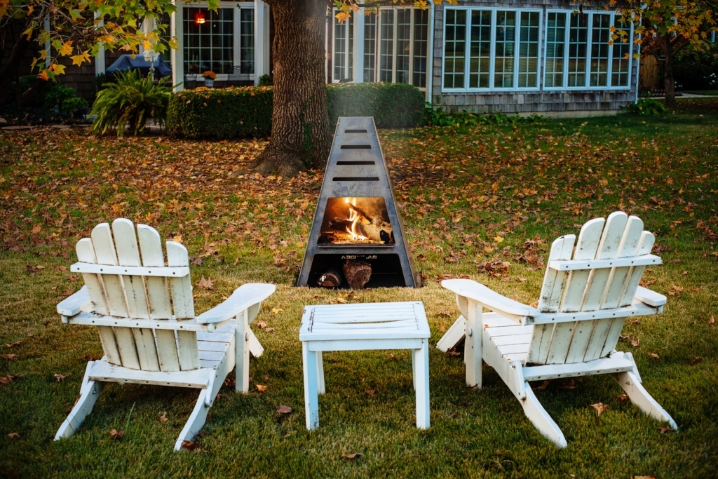 Metal Chiminea Burning Wood with Adirondack Chairs