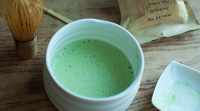 matcha in bowl with whisk and bodhi organics ingredients to make matcha tea