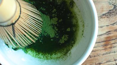 stirring organic matcha with whisk making matcha