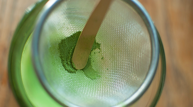 matcha being stirred with the wooden spoon