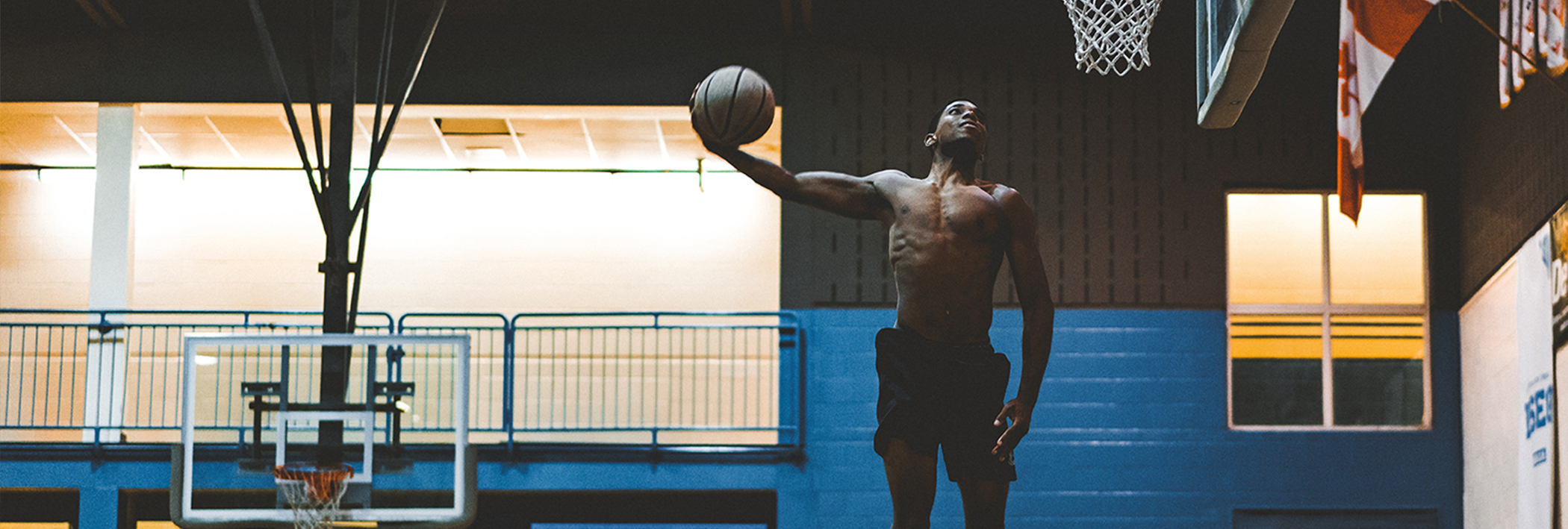 Man in the air about to slam dunk - ithriveX all-natural pain relief cream can soothe sore muscles and joints.