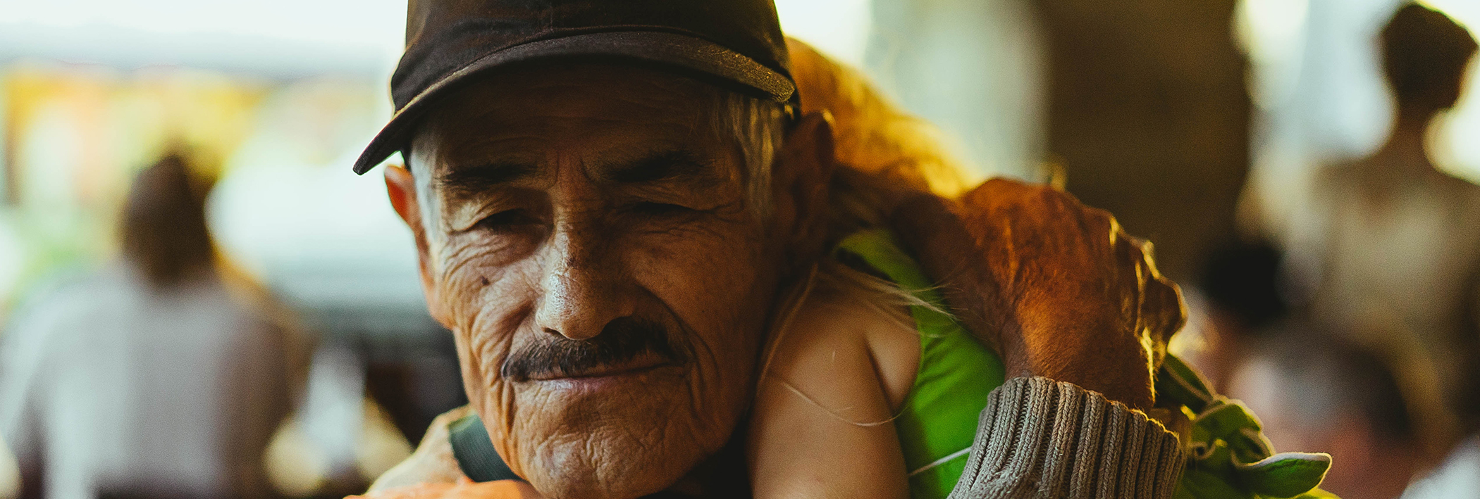 Elderly man holding his grandchild - ithriveX pain relief cream soothe aching muscles and joints associated with aging.