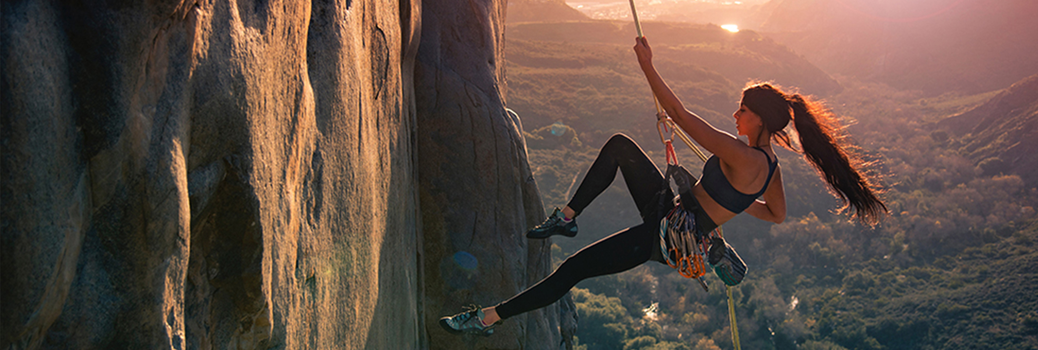 Woman rock climber scaling a rock wall - ithriveX pain relief cream provides relief for sore muscles and joints.