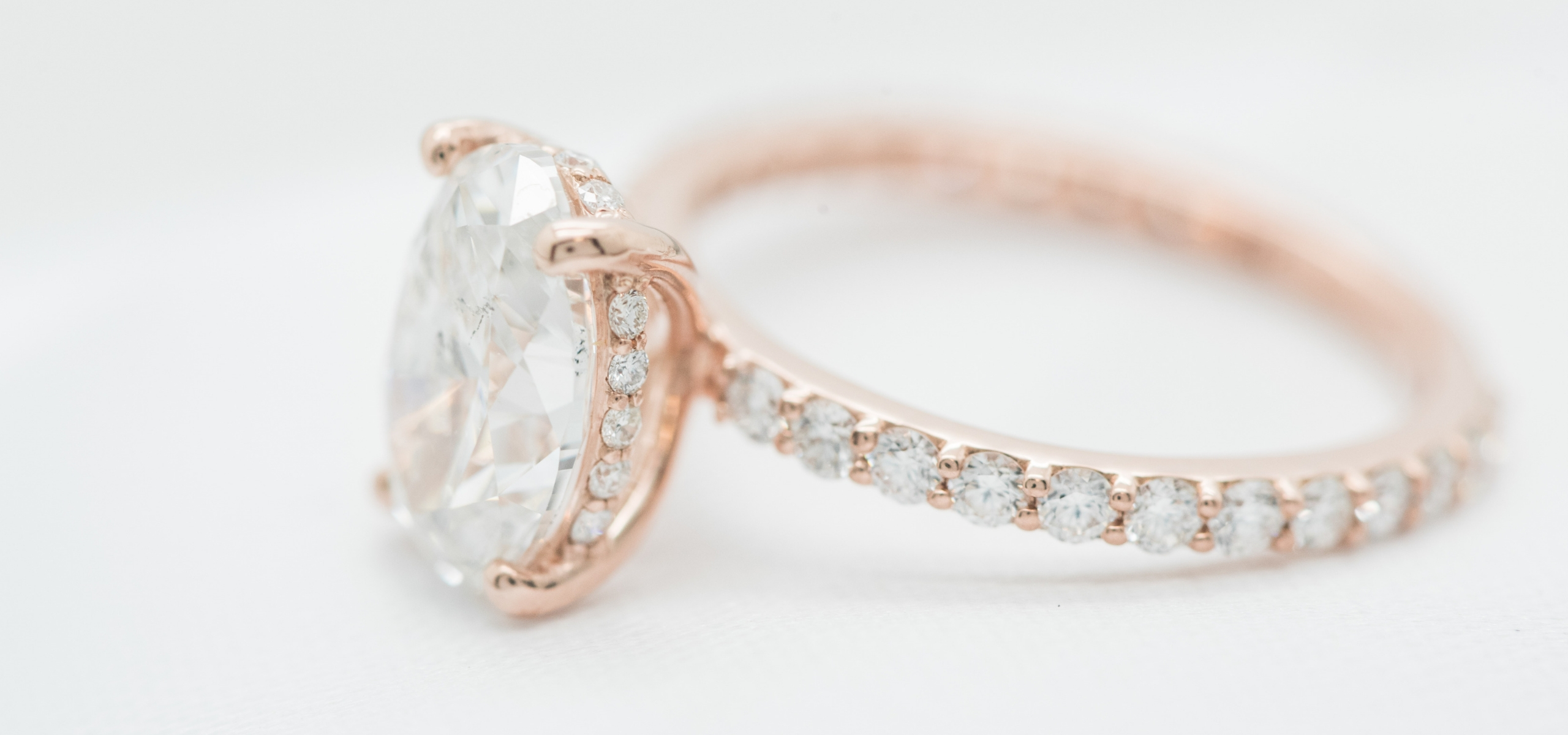 rose gold oval custom engagement ring with diamonds on the band and a hidden halo