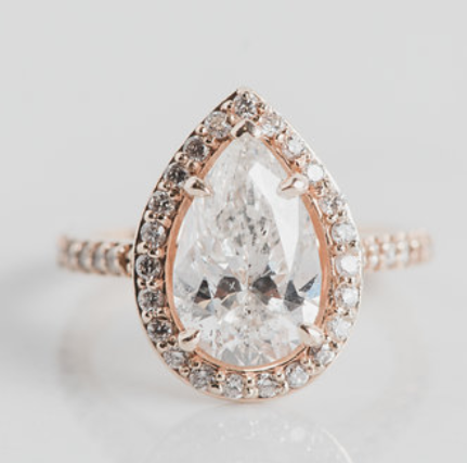 pear shaped solitaire custom engagement ring with a diamond halo