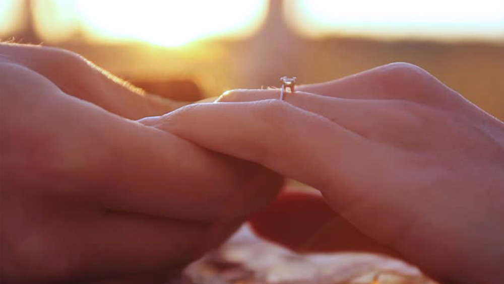 Holding hands after proposing with a ring from Australian Diamond Network